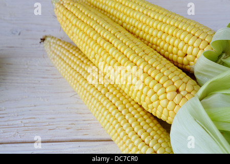 Three fresh corn cobs on the table, food - Stock Photo