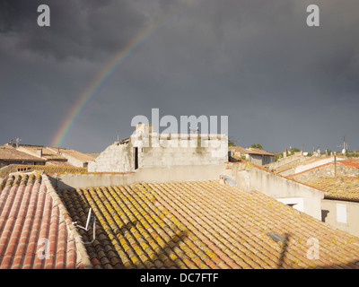 Rainbow over a roof tops Ginestas, France - Stock Photo