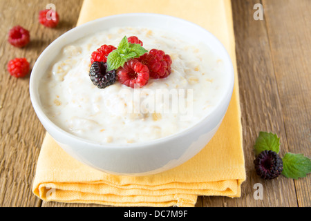 Fresh hot oatmeal porridge with raspberry and mint on napkin and wooden table, close up, horizontal. Healthy vegetarian - Stock Photo