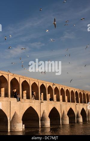 Si-o-Seh Bridge, Isfahan, Iran, with people on the bridge and gulls in the sky - Stock Photo