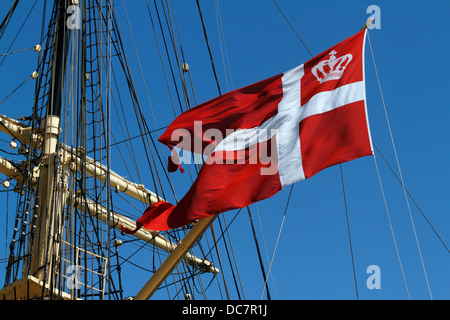 The official swallow-tailed Danish flag, the Dannebrog, on old tall ship, the Danish training ship DANMARK moored - Stock Photo