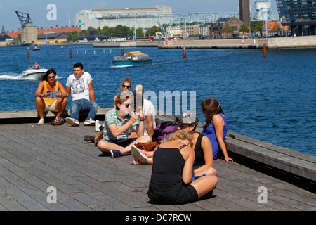 Young people on pier at the Royal Playhouse close to Nyhavn inner harbour in Copenhagen on sunny and hot summer - Stock Photo