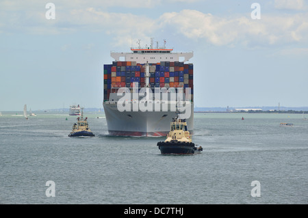 Container ship  in Southampton Waters  with two tugs assisting ship to its docking berth at Southampton , UK - Stock Photo