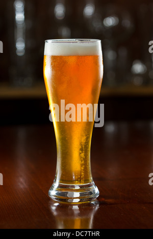 beer served in a chilled glass on a dark bar - Stock Photo