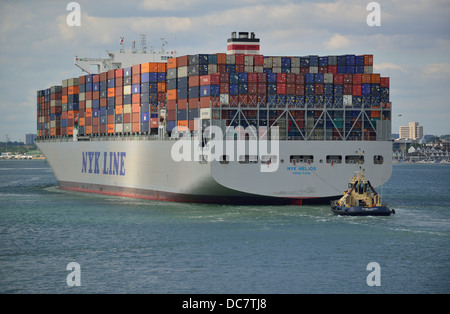 Container ship  in Southampton Waters  with a rear brake tug assisting ship to its docking berth at Southampton - Stock Photo