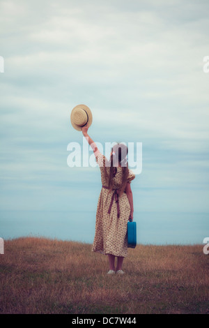 a girl in a vintage dress with suitcase holding a hat - Stock Photo