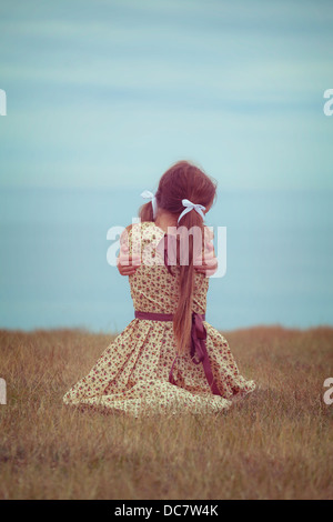 girl in a vintage dress, sitting on a meadow, hugging herself - Stock Photo