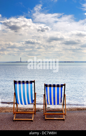 Two blue and white stripped empty deckchairs on Southend seafront - Stock Photo