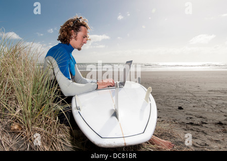 male surfer sitting on beach with laptop on surfboard, Ngarunui Beach, Raglan, New Zealand - Stock Photo