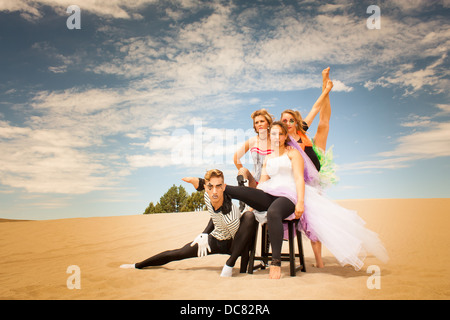 A troupe of acrobatic circus performers pose against a moody desert sky - Stock Photo