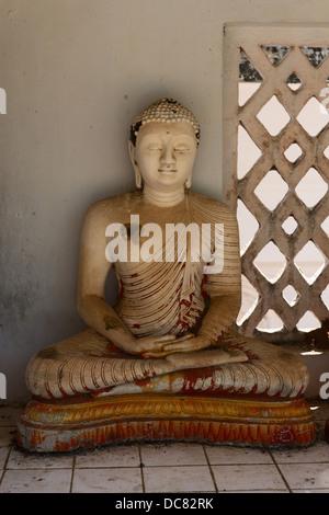 Small grunge Buddha statue in a niche, Avukana, Sri Lanka - Stock Photo