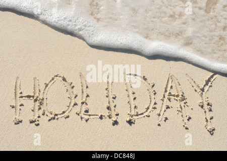 The Word 'Holiday' Written in the Sand on a Beach - Stock Photo