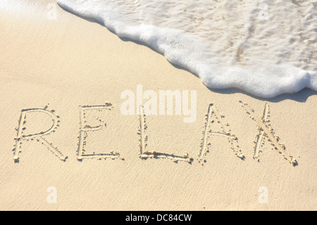 The Word 'Relax' Written in the Sand on a Beach - Stock Photo