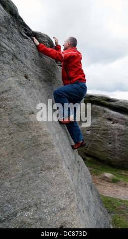 rock climber Doug Blane bouldering at Burbage Edge South, Derbyshire, Peak District National Park, England, UK, - Stock Photo