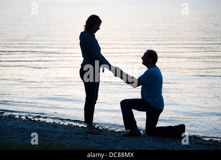 A man is doing a marriage proposal to his girlfriend - Stock Photo