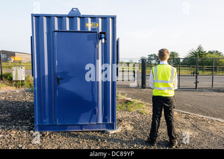 A security guard stands beside his hut inside a fenced off construction site compound - Stock Photo