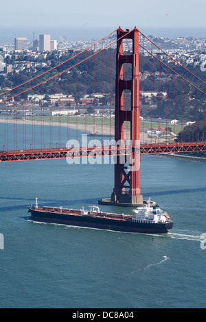 Aerial view of cargo ship passing under Golden Gate Bridge from cliffs on north side of San Francisco California - Stock Photo