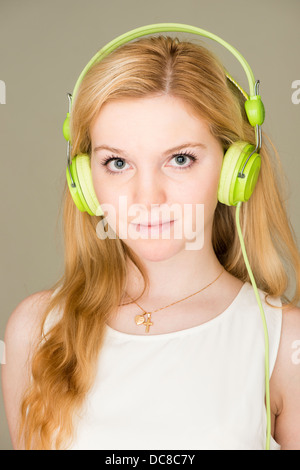 Portrait of young blond female teenager listening to music - Stock Photo