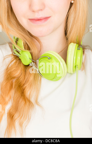 Closeup of young blond female teenager with green headphones - Stock Photo