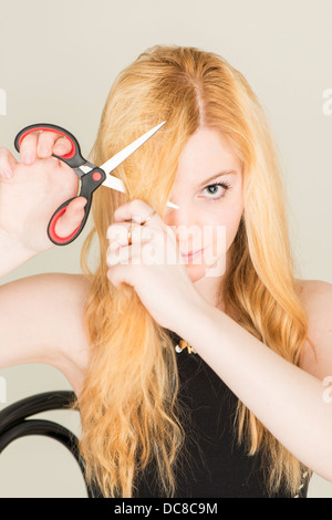 Portrait of young blond female teenager cutting her hair with scissors - Stock Photo