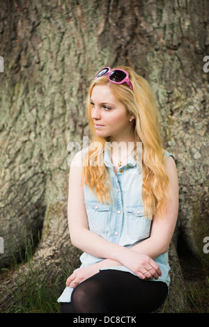 One young blonde attractive woman in front of tree in a park - Stock Photo