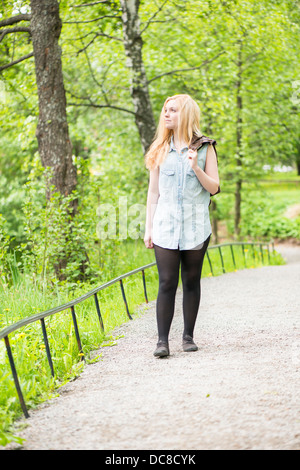 Nature scene with one young attractive woman leaning against  a tree in a park - Stock Photo