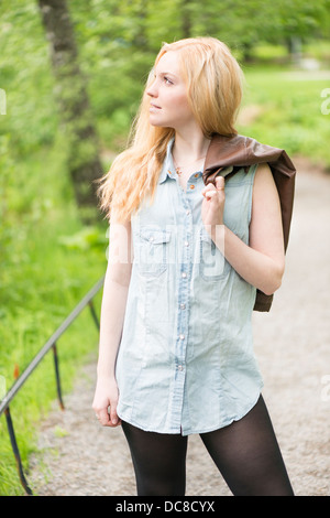 Nature scene with one young attractive woman standing in a park at summertime - Stock Photo