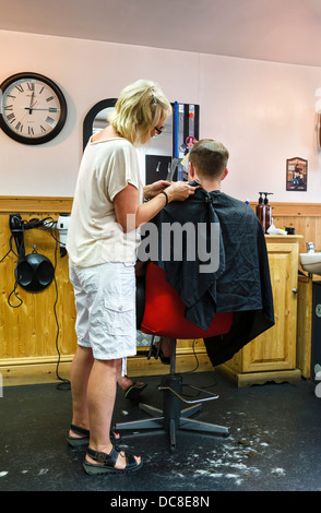 Young man getting a haircut in a barber's shop in Holmfirth, West Yorkshire, England, UK - Stock Photo