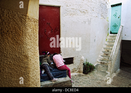 Girls doing homework in the quiet streets of Moulay Idriss. Morocco - Stock Photo