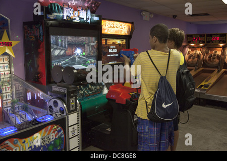 Kids always are in battle mode with the violent games at a video arcade in Coney Island, Brooklyn, NY. - Stock Photo
