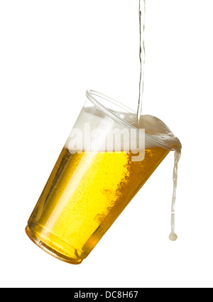 Pouring lager beer into a plastic disposable pint glass - spilling out / over - Stock Photo