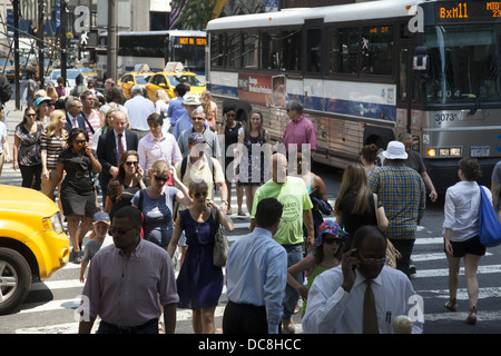 People cross the street at the always crowded intersection of 5th Avenue & 42nd Street, New York City. - Stock Photo