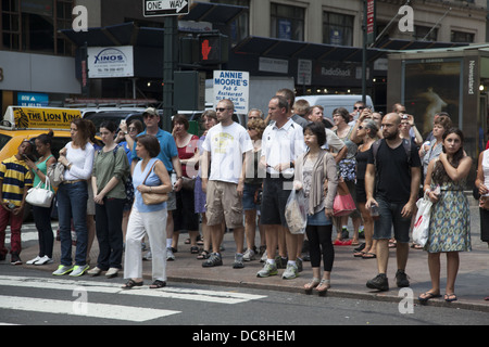 Mostly summer tourists wait for the walk signal to cross the street on 42nd St. near Grand Central Station. - Stock Photo