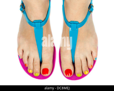 Female legs in summer shoes with a colored pedicure. Isolated on white - Stock Photo