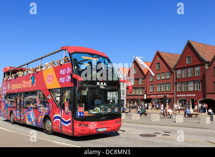 Official tourists' red Hop On Hop Off open top city sightseeing bus in old Bryggen, Bergen, Hordaland, Norway, Scandinavia - Stock Photo
