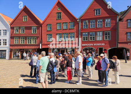 Tourists group by 14th century medieval wooden Hanseatic buildings on waterfront in old harbour district of Bryggen, - Stock Photo