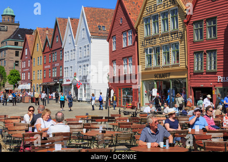 People dining out in outdoor pavement cafe on waterfront by Bergen's historic wooden buildings in summer. Bryggen - Stock Photo