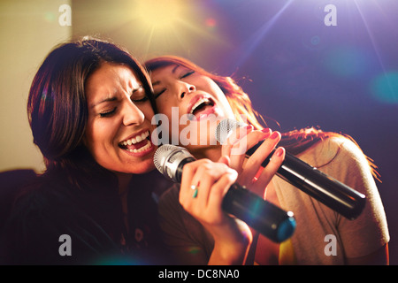Two women singing karaoke. - Stock Photo