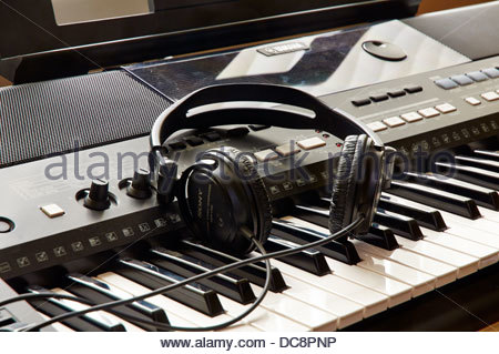 pair sony headphones on the piano keys of a yamaha electronic digital keyboard musical instrument - Stock Photo