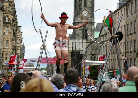 Edinburgh, Scotland, UK, Monday, 12th August, 2013. A Street Performer juggling and slack rope walking on the Royal - Stock Photo