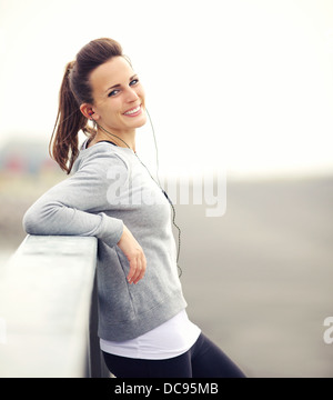Smiling woman having her break after running - Stock Photo