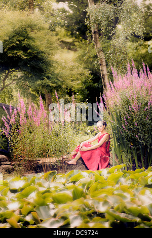 beautiful girl in a garden with pond and pink flowers - Stock Photo