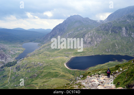 Walker descending on path from the Welsh Mountain Y Garn with Tryfan and the lakes Lyn Ogwen & Llyn Idwal in the - Stock Photo