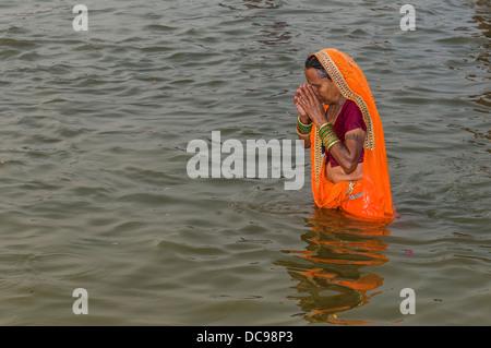 Woman wearing an orange sari taking a bath in the Sangam, the confluence of the rivers Ganges, Yamuna and Saraswati, - Stock Photo