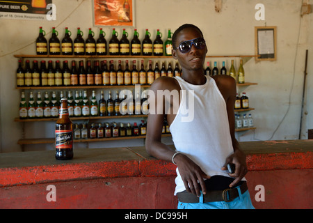 Contemporary dressed Himba man with a beer bottle in a shebeen, a bar