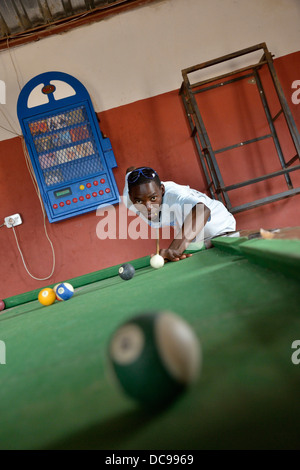 Young Himba man playing billiards in a bar - Stock Photo