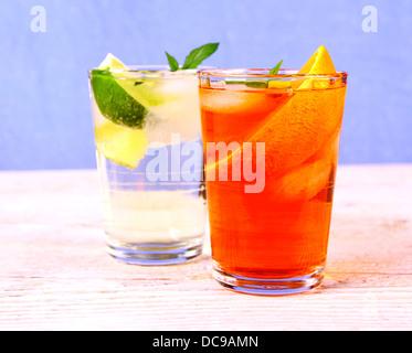Orange and elderflower cocktails on blue background, close up - Stock Photo