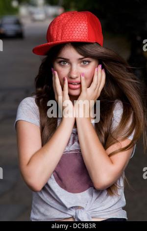 surprised beautiful emotional teen model on street. red cap, grey t-shirt, dark blue shorts - Stock Photo