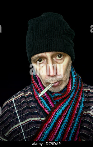 Sick man with the flu and temperature, wearing a cap and a woolen scarf, on dark background - Stock Photo