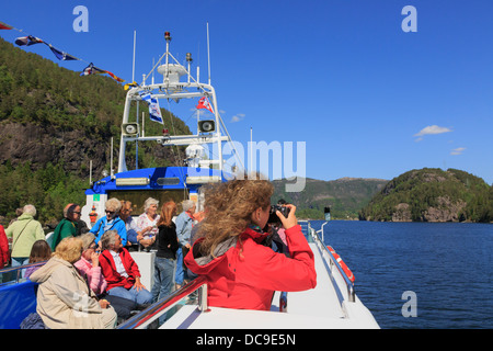 Woman taking a photograph on a tourists sightseeing cruise boat along Osterfjorden fjord from Bergen, Hordaland, - Stock Photo